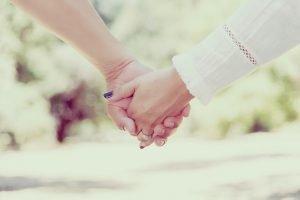 Paar hält Händchen auf Tisch.